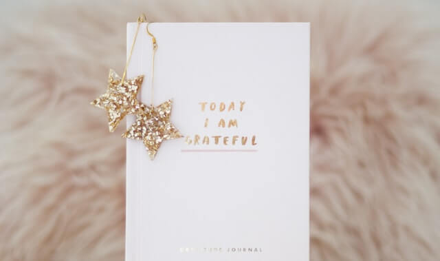 A white notepad with gold star earrings and a message Today I am Grateful lies on a fluffy pale pink rug | bucketlistmylife.com - Bucket list Ideas You Can Do in 2021